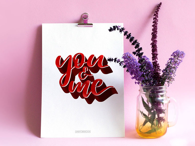 "DIN A3 Plakat lehnend an einer rosa farbenen Wand mit dem hangeletterten Schriftzug ""you & me"" mit 3D Effekt Schatten in Rot"